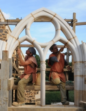 Stonemasons at work on a tracery window at Guédelon castle, France