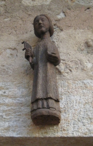 wooden statuette of a woman holding a trivet, on a stone wall
