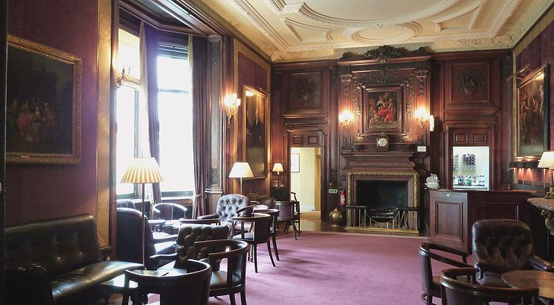 a room with ornate panelling, tables and chairs, the Savile Club in London
