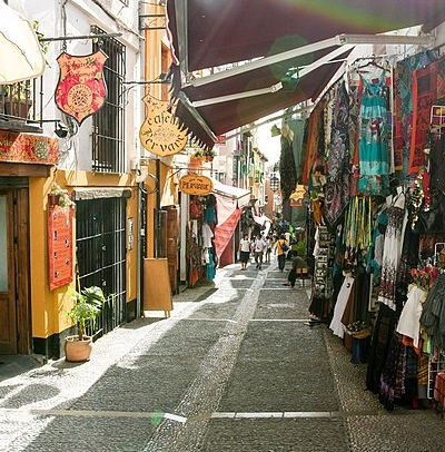 a cobbled street lined with shops with bright clothing hanging outside -